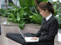 Business woman with a laptop. Business woman working on laptop in the hall of office building Royalty Free Stock Photo