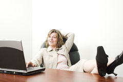 Business woman with laptop. Business woman with feet on table in boardroom Royalty Free Stock Photography