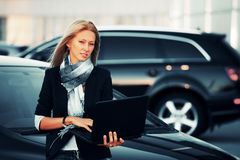 Fashion business woman with laptop at the car Royalty Free Stock Photography