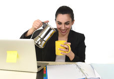 Business woman at laptop computer desk drinking coffee excited and anxious in caffeine addiction. Young attractive business woman at laptop computer desk pouring Stock Photo
