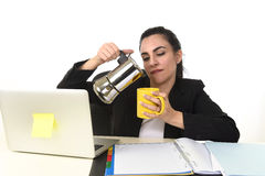 Business woman at laptop computer desk drinking coffee excited and anxious in caffeine addiction. Young attractive business woman at laptop computer desk pouring Royalty Free Stock Images