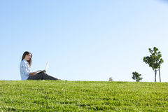 A business woman on a laptop in a field Stock Photography