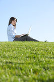 A business woman on a laptop in a field Royalty Free Stock Photos