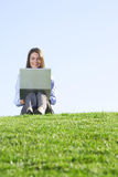 A business woman on a laptop in a field Royalty Free Stock Image