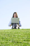 A business woman on a laptop in a field Stock Image