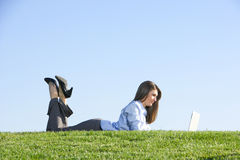 A business woman on a laptop in a field Royalty Free Stock Photo