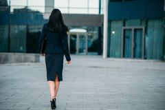 Business woman with laptop in hands, back view. Business woman with eyeglasses and laptop in hands, back view. Modern building, financial center, cityscape Royalty Free Stock Photos