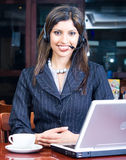 Business woman with laptop and headset. Closeup face of smiling indian business woman with headset and laptop computer Royalty Free Stock Photos