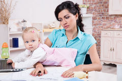 Business woman with laptop and her baby girl. Young business women with laptop and her baby girl Stock Image