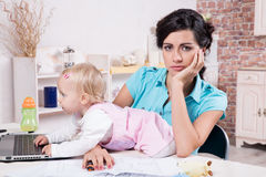 Business woman with laptop and her baby girl Stock Image