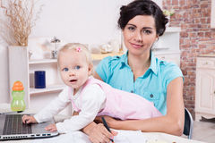 Business woman with laptop and her baby girl Stock Photos