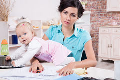 Business woman with laptop and her baby girl. Young business women with laptop and her baby girl Royalty Free Stock Photos