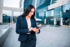 Business woman with laptop outdoor. Business woman with laptop. Modern building, financial center, cityscape. Female businessperson in suit Royalty Free Stock Photo
