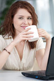 Business woman with a laptop and mug Stock Photography