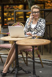 Business woman with laptop sitting in cafe in the street and talking on the cell phone. Stock Image