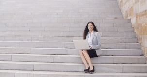 Business woman with laptop on stairs Royalty Free Stock Image