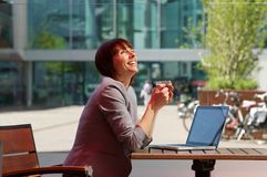 Business woman laughing with cup of tea and laptop Royalty Free Stock Photography