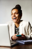 Business woman laughing with laptop and mobile phone Stock Photo