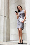 Business woman lawyer reading app on smartphone. Business woman lawyer using apps on smartphone outside to read news or text sms. Successful young multiracial Royalty Free Stock Photography