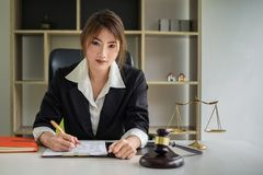 Business woman or lawyers discussing contract papers with brass scale on wooden desk in office. Law, legal services, advice,. Justice and real estate concept stock photography