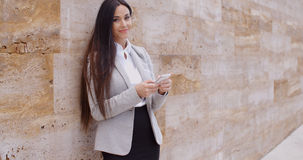 Business woman leaning against wall texting Stock Images