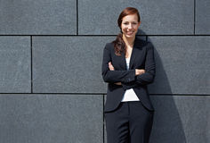 Business woman leaning on wall Royalty Free Stock Image