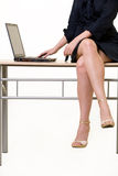 Business woman legs. Legs and body of a business woman sitting on a desk working on laptop on a light colored background Royalty Free Stock Photography
