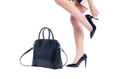 Business woman legs with black shoes and leather handbag Stock Image