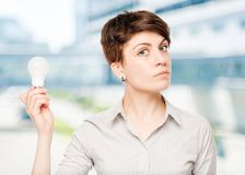 business woman with a light bulb in hand stock photos