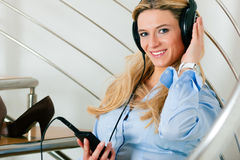 Business woman listening music at home. Sitting relaxed on the stairs Royalty Free Stock Images
