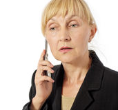 Business woman listens to smb on mobile phone Royalty Free Stock Image