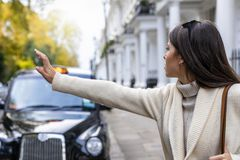 Business woman in London hailing for a black taxi. On the street, United Kingdom royalty free stock image