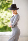 Business woman in a long dress. Beautiful female in a black hat. Glamorous and sensual girl with red lips on a green stock images