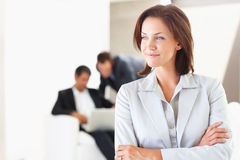 Business woman looking away with colleagues behind Stock Photography
