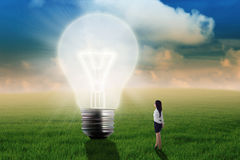 Business woman looking at big light bulb Stock Image