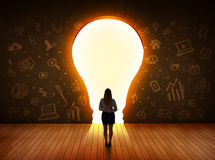 Business woman looking at bright light bulb in the wall Royalty Free Stock Photography