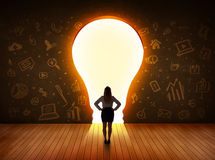 Business woman looking at bright light bulb in the wall Stock Photography