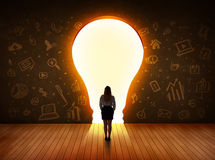 Business woman looking at bright light bulb in the wall Royalty Free Stock Photo