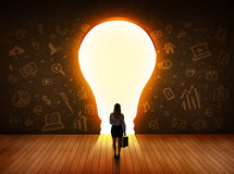 Business woman looking at bright light bulb in the wall Royalty Free Stock Photos