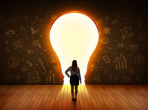 Business woman looking at bright light bulb in the wall Stock Photos