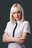 Business woman looking at the camera with crossed arms on a gray Royalty Free Stock Photography