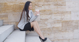 Business woman looking at coffee cup Royalty Free Stock Photos