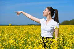Business woman looking into the distance and point. Young girl in yellow flower field. Beautiful spring landscape, bright sunny da Stock Photo