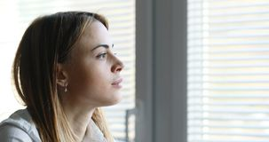 Business woman looking into the future. Portrait of a business woman looking at camera and then, turning her sight to the window and outside into the future stock footage