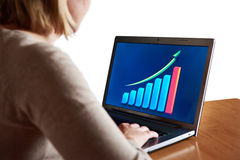Business woman looking at graph of growth indicators on laptop Stock Photo