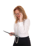 Business woman looking at her clipboard. Royalty Free Stock Photography