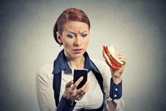 Business woman looking at her mobile phone eating bread sandwich. Portrait of a young worried business woman looking at her mobile phone eating bread sandwich on Royalty Free Stock Photos