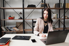 Business woman looking at her phone while working Royalty Free Stock Photos