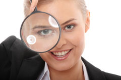 Business woman looking into a magnifying glass Royalty Free Stock Image