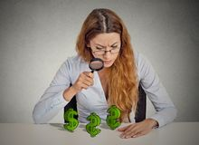 Business woman looking through magnifying glass at dollar signs Royalty Free Stock Photos